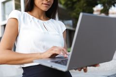 Business woman posing outdoors at the street using laptop computer. Cropped photo of a beautiful business woman posing outdoors at the street using laptop royalty free stock images