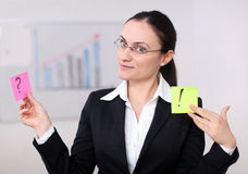 A business woman with postit. Business woman holding post its in an conference room Royalty Free Stock Images