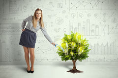 Business woman pouring water on lightbulb growing tree Royalty Free Stock Photography