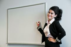 Business woman present with draw board on white background. And look at the audience with confident looking Stock Photos