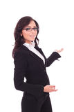 Business woman presenting in back. Young business woman presenting something in the back while looking at the camera with a smile on her face. on white Stock Photography