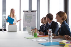 Business woman presenting project to her colleagues. Business women presenting project to her colleagues in modern office Royalty Free Stock Photos