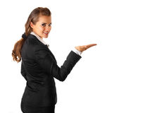 Business woman presenting something on empty hands. Smiling modern business woman presenting something on empty hand isolated on white background Royalty Free Stock Image
