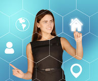 Business woman presses home icon located in Royalty Free Stock Photo