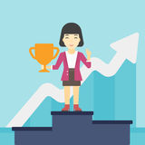 Business woman proud of her business award. An asian business woman standing on a pedestal with winner cup. Business woman celebrating her business award Stock Photos