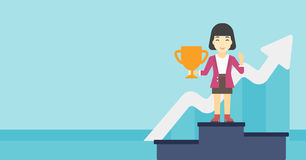 Business woman proud of her business award. An asian business woman standing on a pedestal with winner cup. Business woman celebrating her business award Royalty Free Stock Photography