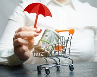 Business woman provides protection for a supermarket trolley with money. Guarantee of protection of foreign investment. In the economy, favorable conditions for royalty free stock photo