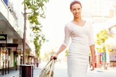 Business woman pulling suitcase bag walking in city Stock Photos