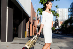Business woman pulling suitcase bag walking in city Stock Photo