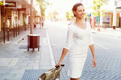 Business woman pulling suitcase bag walking in city Royalty Free Stock Image