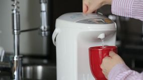 Business woman pushing hot water button on electric thermo pot stock video footage