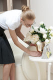 Business woman puts the vase with white peonies  on Royalty Free Stock Image