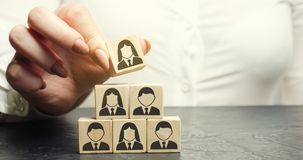 Business woman puts a wooden cube with the image of workers. Mixed staff concept. Personnel management in a team. Human resources stock image