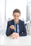 Business woman putting coin into piggy bank Stock Photo