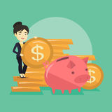 Business woman putting coin in piggy bank. Successful business woman putting money in a big pink piggy bank. Young asian business woman saving her money in Royalty Free Stock Photo