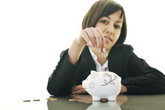 Business woman putting coins money in piggy bank Royalty Free Stock Photos