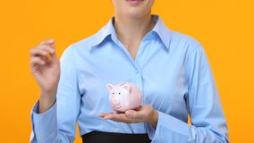 Business woman putting coins in piggy back, project investment, development