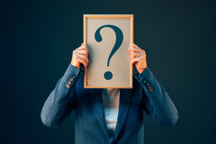Business woman with question mark looking for answers. Businesswoman with question mark looking for answers, questioning and wondering about uncertain future in royalty free stock image