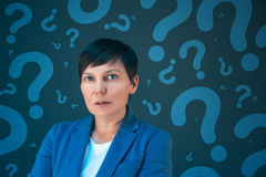 Business woman with question marks looking for answers Stock Image