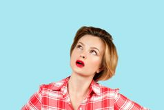 Business woman with questioning face expression looking up. Young thinking business woman with questioning face expression looking up on blue background stock images