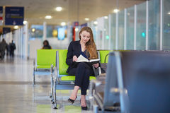 Business woman reading a book in international airport Stock Photography