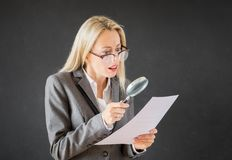 Woman reading business contract with magnifying glass. Business woman reading business contract with magnifying glass royalty free stock image