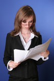 Business woman reading carefully a file. Portret of a young business woman , with eyeglasses, reading a file, suggesting attention, concentration Stock Photography