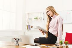 Business woman reading digital tablet at office. Serious business woman in eyeglasses sitting on table in modern office and reading digital tablet, copy space Royalty Free Stock Photography