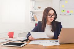 Business woman reading document at office desktop. Paperwork. Serious business woman in formal wear sitting at wooden desk in modern office and reading report Royalty Free Stock Image