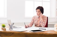 Business woman reading document at office desktop. Paperwork. Serious business woman in formal wear sitting at wooden desk in modern office and reading report Stock Image