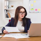 Business woman reading document at office desktop. Paperwork. Serious business woman in formal wear sitting at wooden desk in modern office and reading report Royalty Free Stock Images