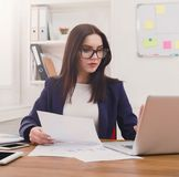 Business woman reading document at office desktop. Paperwork. Serious business woman in formal wear sitting at wooden desk in modern office and reading report Stock Images