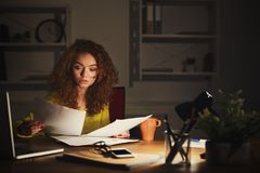Business woman reading document at office desktop. Paperwork. Serious business woman at office at night reading documents. Concentrated female manager working Royalty Free Stock Photo