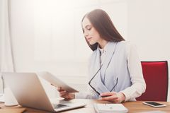 Business woman reading document at office. Paperwork. Serious business woman in formal wear sitting in modern office and reading report document, copy space Stock Photos