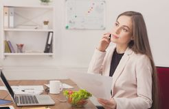 Business woman reading document at office. Paperwork. Serious business woman in formal wear sitting in modern office and reading report document, copy space Stock Photo