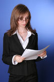 Business woman reading documents. Portret of a young business woman reading sceptical a file Stock Image