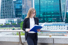 Business woman reading documents folder on the street on a background of skyscrapers Stock Images