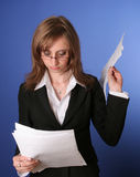 Business woman reading a file. Image of a young business woman, in a black suit, reading disappointed a file Royalty Free Stock Image