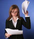 Business woman reading impatiently a file. Image of a young business woman reading impatiently a file,suggesting daily stress Stock Images