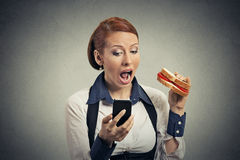 Business woman reading news on smart phone eating sandwich Stock Images