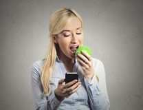 Business woman reading news on smartphone eating green apple Stock Photography