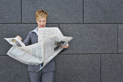 Business woman reading newspaper in windy weather Stock Photography