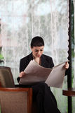Business woman reading paper Stock Photo