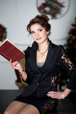 Business woman is reading red book. Beautiful smiling woman with natural make up, stylish hair dress, black business suit costume - skirt lace jacket. Office Stock Photos