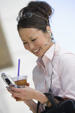 Business Woman Reading Text Message. Beautiful mature business woman reading text message on a cell phone Stock Image