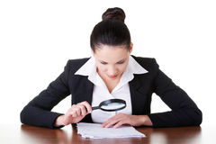Business woman reading though magifying glass. Royalty Free Stock Images