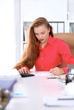 Business woman in red blouse making report, calculating or checking balance. Royalty Free Stock Images