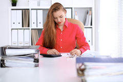 Business woman in red blouse making report, calculating or checking balance. Stock Image