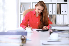 Business woman in red blouse making report, calculating or checking balance. Royalty Free Stock Photo