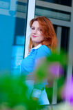 Business woman with red hair in front of office building. Royalty Free Stock Photo
